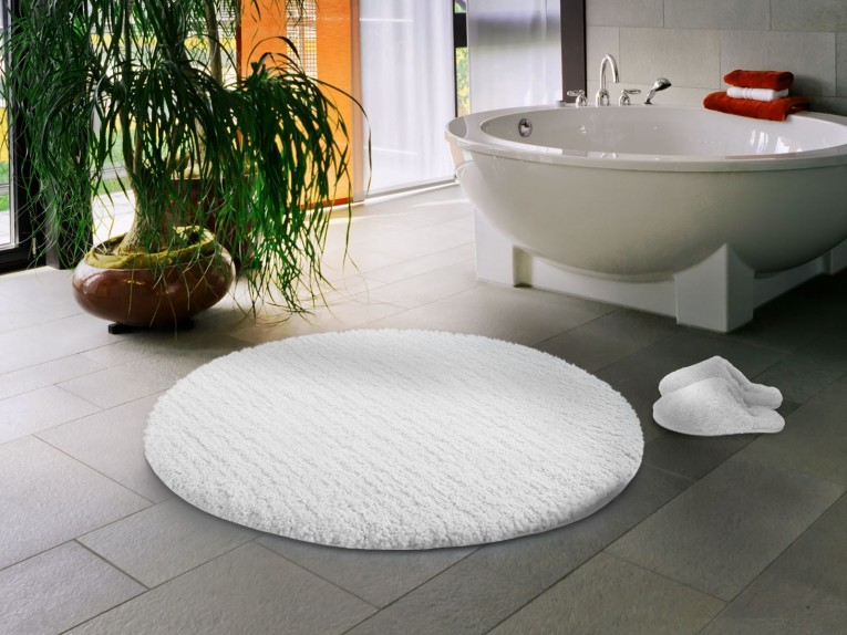 Fascinating White Round Bath Mat With Round Bathtub And Black Stone Floor For Bathroom