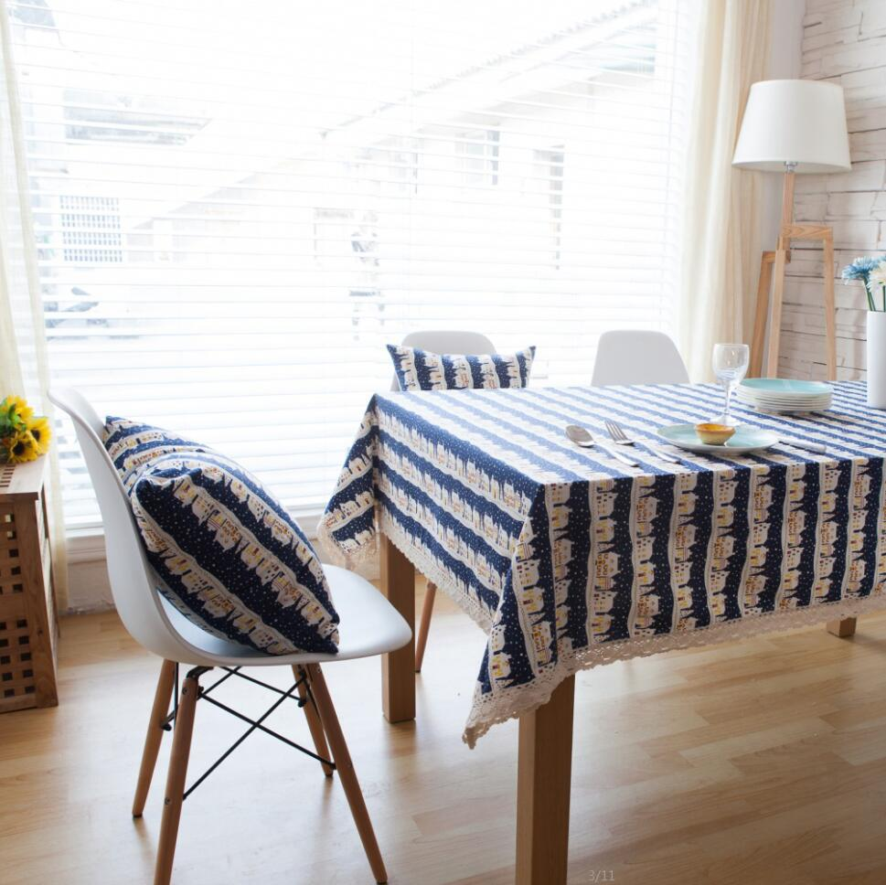 fashionable white dining chairs and blue oblong tablecloth
