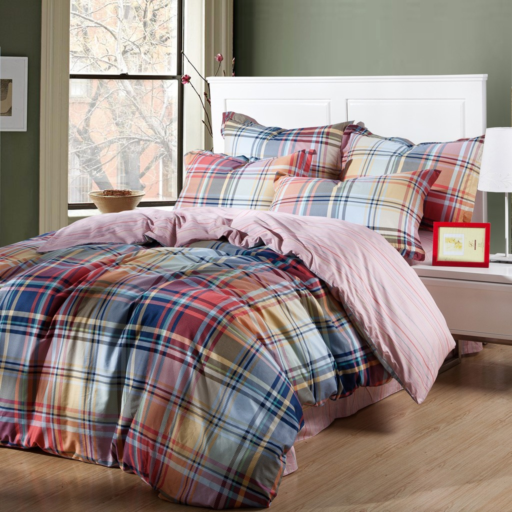Alluring plaid comforter with rugs and wooden floor plus headboard and sidetable also pillows