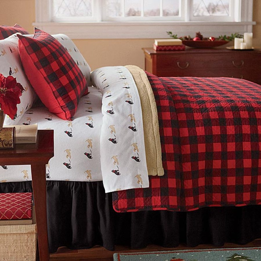Comfy plaid comforter with rugs and wooden floor plus headboard and sidetable also pillows