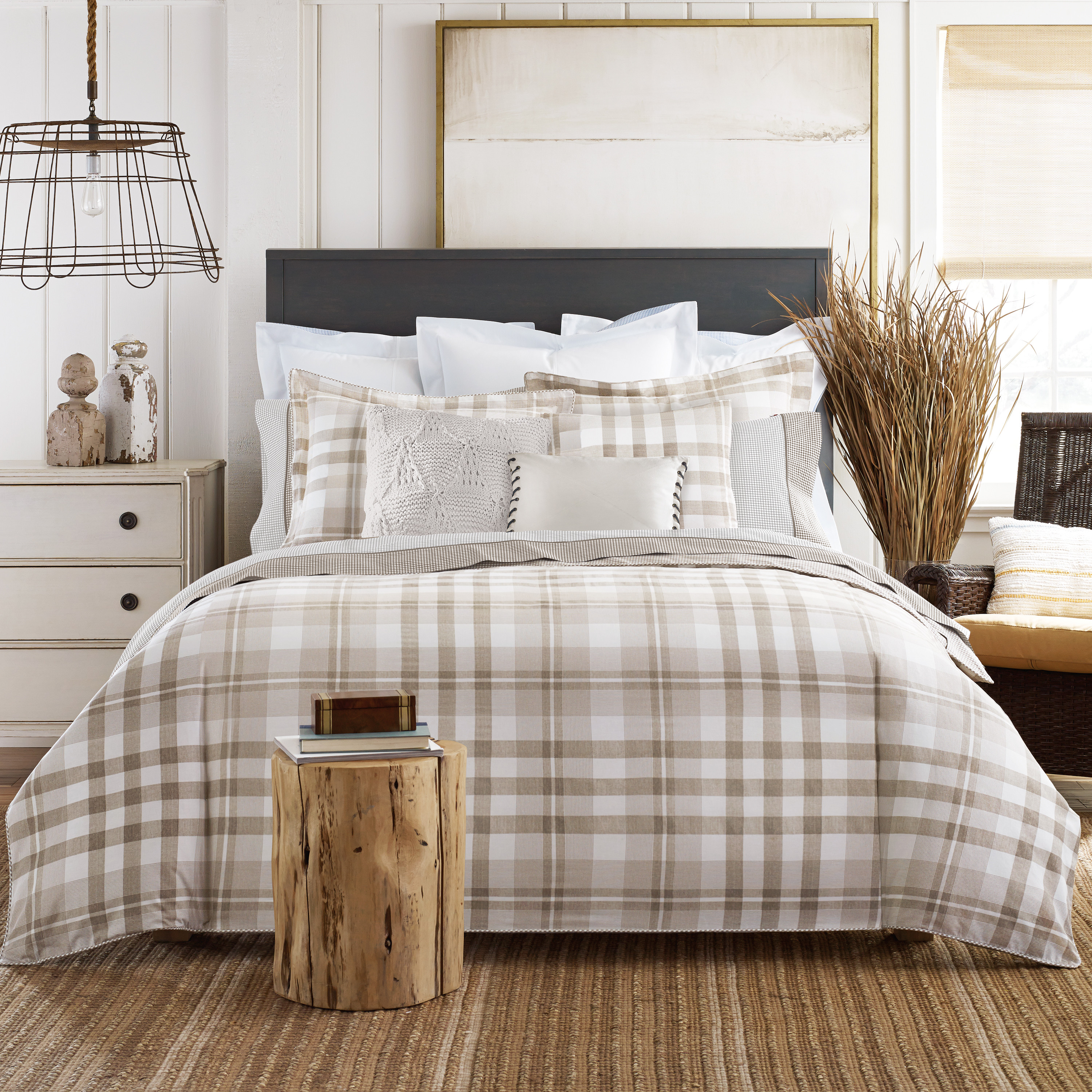 Cozy plaid comforter with rugs and wooden floor plus headboard and sidetable also pillows