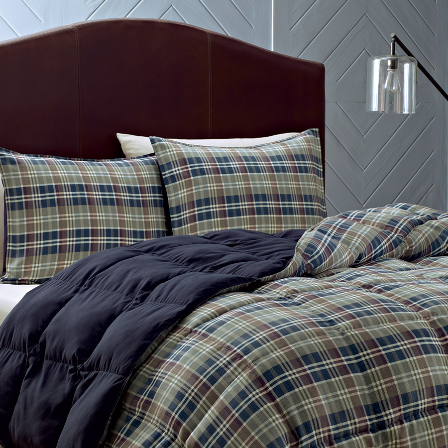 Enchanting plaid comforter with rugs and wooden floor plus headboard and sidetable also pillows