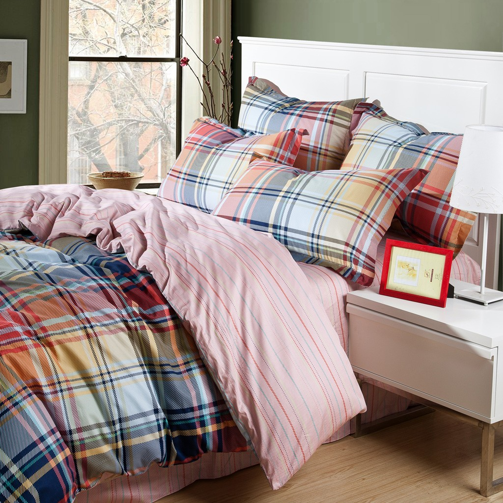Endearing plaid comforter with rugs and wooden floor plus headboard and sidetable also pillows