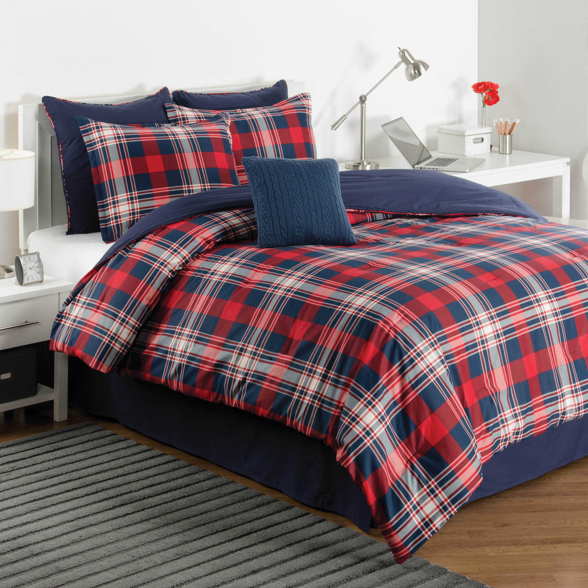 Exciting plaid comforter with rugs and wooden floor plus headboard and sidetable also pillows