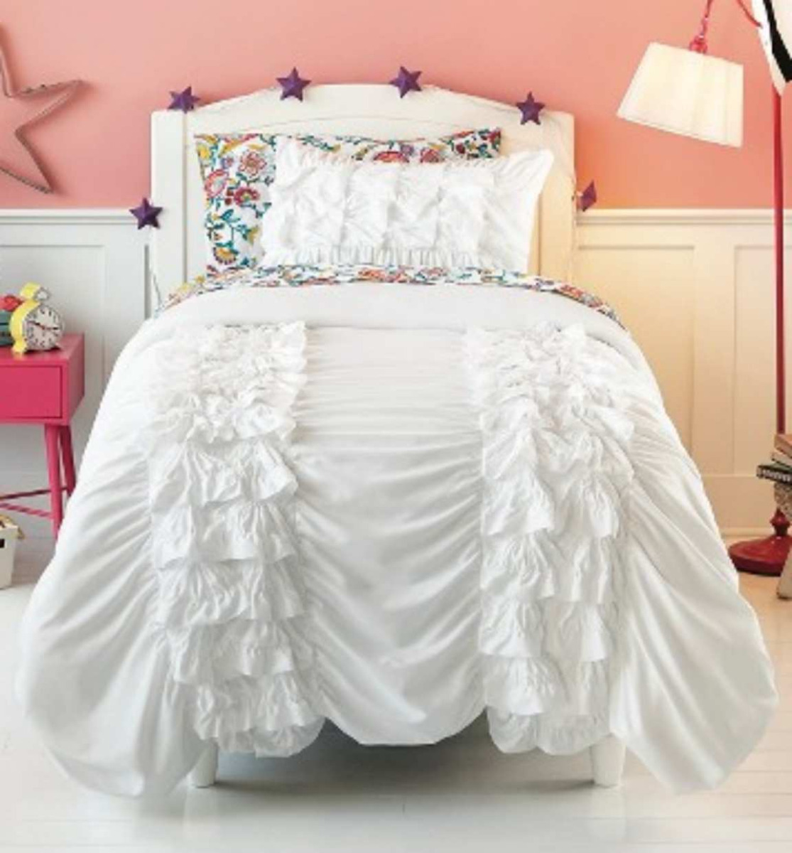 white bed ruffle comforter and arc stand lamp